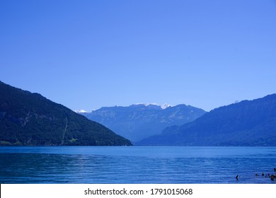 Blue mountain range and tranquil lake against a clear blue sky backdrop