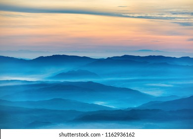 Blue mountains and hills under beautiful orange sunset