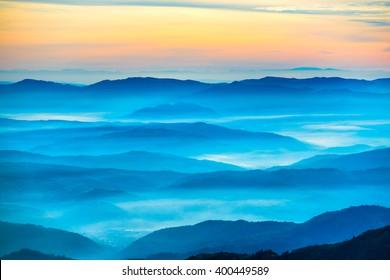 Blue mountains and hills under beautiful orange sunset