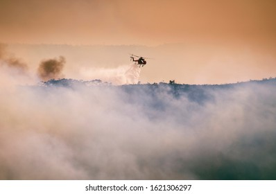 The Blue Mountains, New South Wales / Australia - December 1st 2019: NSW Rural Fire Service drop water from a helicopter onto Mega Fire.