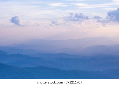 Blue mountains with pastel fog and clouds