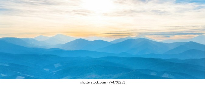 Blue mountains at sunset sky. Panorama view of peaks ridge