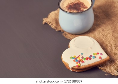 Blue mug of coffee with foam on sackcloth near gingerbread cookie in shape of heart on concrete surface. Concept of love or christmas. Toned and vintage image