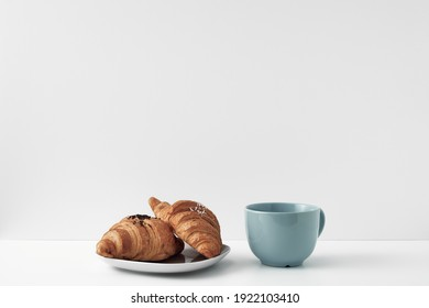 Blue mug and croissants on a white background. Eco-friendly and natural materials in the decor, dessert. Copy space, mock up