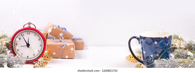 Blue mug with hot tea, coffee or cocoa, fir tree branches  and red clock on white textured  background.  Site header. Long banner formate. Selective focus. Place for text.