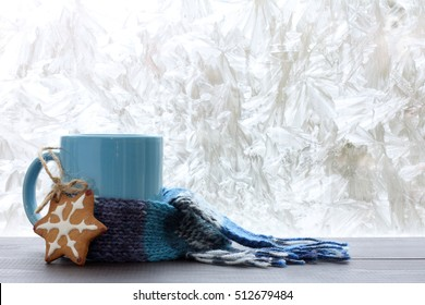 blue mug with a warm scarf and homemade cakes on the background of frozen window / drinks for the winter season