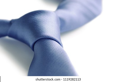 Blue neck tie on white background. Close-up view of the knot