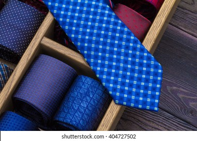 blue necktie on top of group of coiled neckties on table