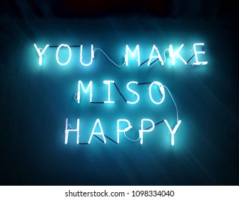 A blue neon light 'You make miso happy' is a romantic quote or phase , 'miso' is synonym to 'me so'