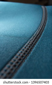 Blue neoprene scuba diving, snorkeling or surfing wetsuit - close up of stitching.