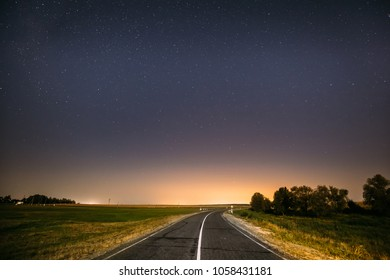Blue Night Starry Sky Above Country Asphalt Road In Countryside And Green Field. Yellow City Lights On Background. Night View Of Natural Glowing Stars