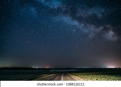 Blue Night Starry Sky Above Country Asphalt Road In Countryside And Green Field. Night View Of Natural Glowing Stars And Milky Way Galaxy.