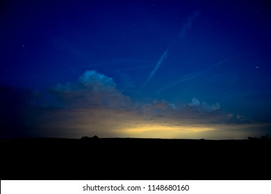 Blue Nightsky with Stars and Clouds over Silhouette Landscape