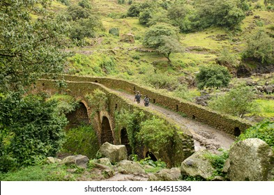 BLUE NILE WATERFALL, ETHIOPIA - AUGUST 06, 2014: two unidentified shepherd walk on the 17th-century Portuguese bridge which was the first bridge to span the Blue Nile.