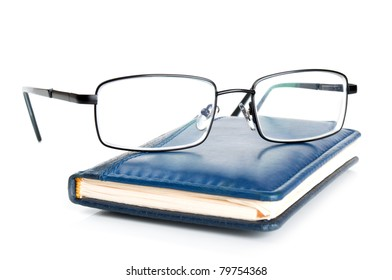 blue notebook and glasses isolated on a white background