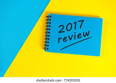 Blue notepad with review 2017. New year 2018 - Time to summarize and plan goals for the next year. Business background