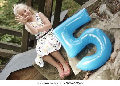 Blue number 5 sign and cute girl wearing summertime dress celebrating her 5th birthday