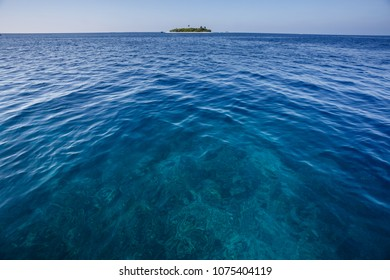 Blue ocean with coral reef and small tropical island in the distant  background
