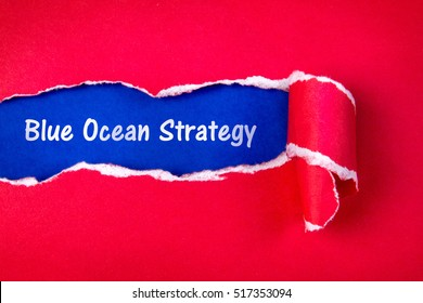 Blue ocean strategy word on Torn red Paper and space with  a blue paper background