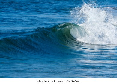Blue ocean and surf with waves on bright, sunny day.
