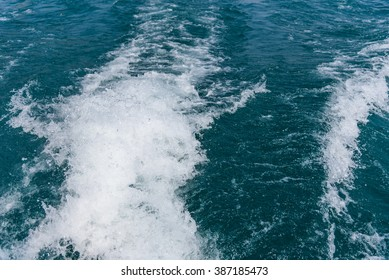 Blue ocean wake from cruise ship. Bright on summer day.