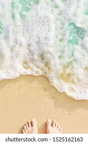 Blue ocean wave and human foots on the sandy beach background, view from above