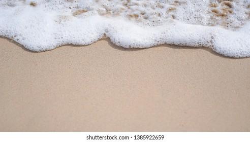 Blue ocean wave on sandy beach background