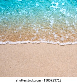 Blue ocean wave on sandy beach background