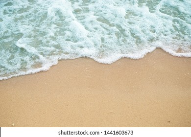 Blue ocean wave on sandy beach
