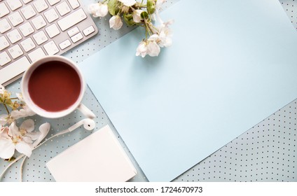 blue office desk background with smartphone with blank screen mockup, laptop computer, cup of coffee and supplies. Top view with copy space, flat lay.