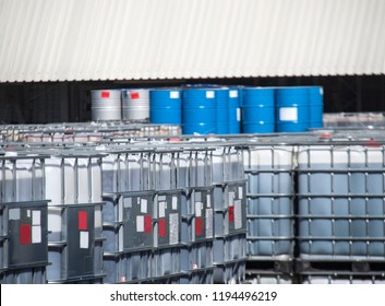 Blue oil drums and white IBC container on a chemical storage site