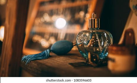 A blue old fashion glass perfume container on a wooden shelf.