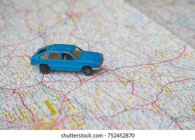 A blue old toy car on a map
