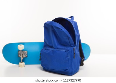 Blue open backpack next to skateboard on white background, back to school