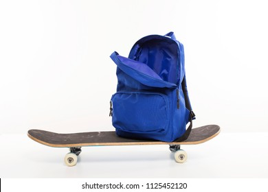 Blue open backpack sitting on skateboard, back to school concept