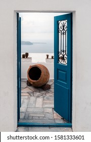 Blue opened door, concrete walls with ancient vase. Entrance to a house with vintage look. Oia, Santorini, Greece.