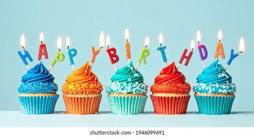 Blue and orange birthday cupcakes spelling happy birthday