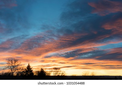 Blue and orange cloud formations against soft blue sunrise sky with dark tree silhouttes in foreground on Winter morning. Photo shot locally December 2017.