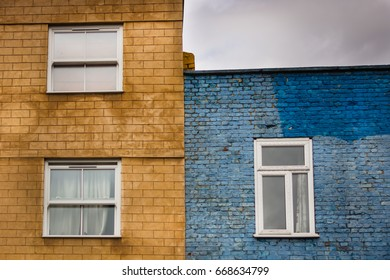 Blue and orange facade with windows of two buildings in Camden, London