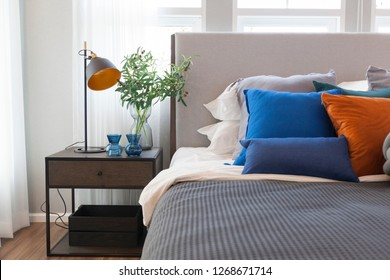 Blue and orange pillows on bed with grey blanket in modern style bedroom. With modern lamp and plant pot on side table.
