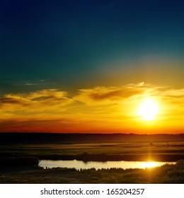 blue and orange sunset over lake