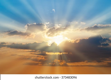 Blue and orange sunset sky with rays of sun. Natural landscape for background