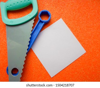 blue and orange toy tools, a white sheet of paper on a dark orange background. saw, bolts and nuts and other toy tools. place for text