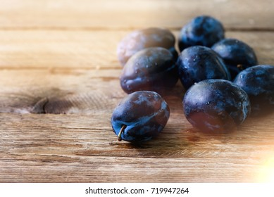 Blue organic plums on dark wooden background. Copyspace.