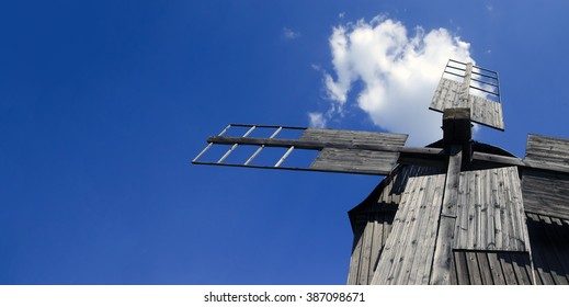blue original windmill. Old wooden windmill on the blue sky background