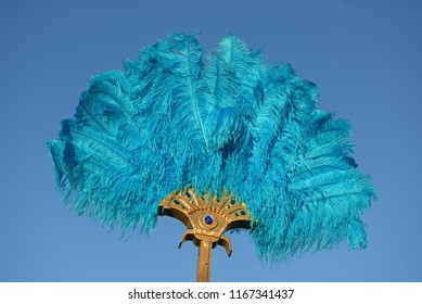 A blue ostrich feather fan stands out against a blue sky