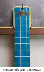 Blue outdoor shower made of cement and tile.