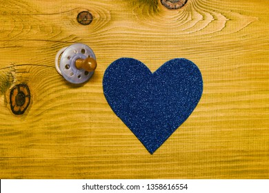 Blue pacifier for baby boy  with heart shape on wooden table.Baby announcement concept.Toned photo.