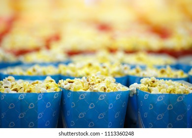 Blue package with popcorn. It can be seen that there are also a lot of popcorn in the background, in anticipation of a good movie in the cinema.