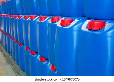 Blue packaging with red caps for packing chemicals is stacked and organized inside warehouse. Plastic buckets for keeping the quality of chemicals
